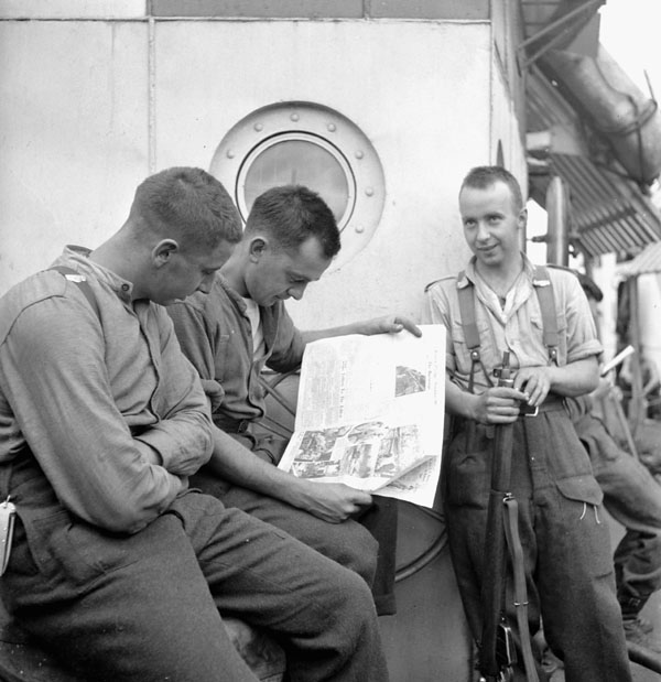 Infantrymen of the 9th Canadian Infantry Brigade aboard an LCI, reading the news of the Canadian entry into Rome.