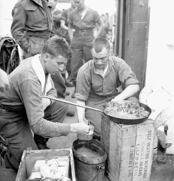 Infantrymen of The Highland Light Infantry of Canada cooking a meal aboard LCI 306.