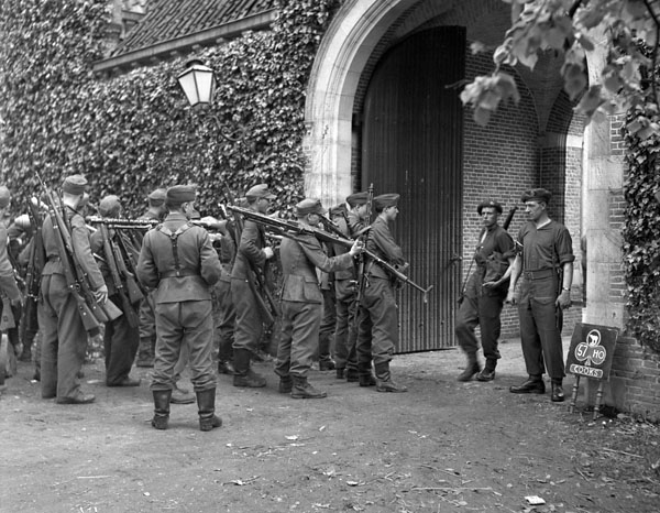 German soldiers entering a concentration area to be disarmed by soldiers of the 1st Canadian Corps