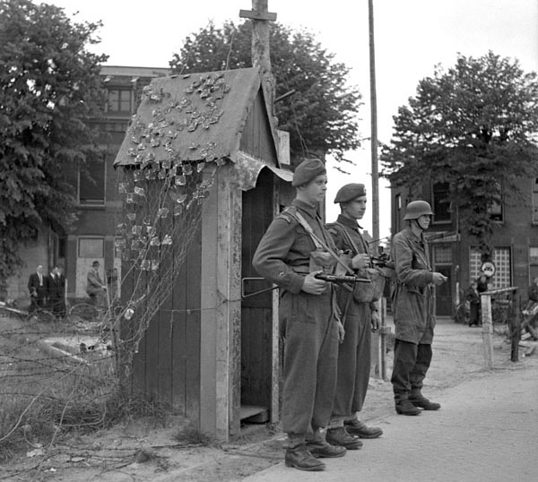 Canadian Corps soldiers on guard duty with a German soldier, also on guard duty, at the German prisoner of war garrison